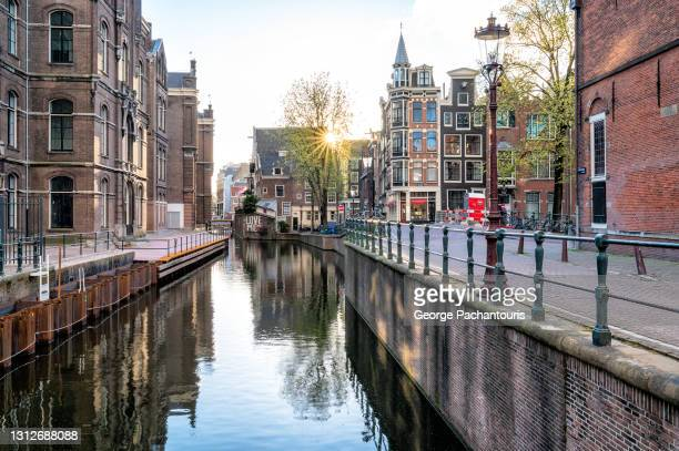 sunset on a canal in amsterdam - amsterdam stock pictures, royalty-free photos & images