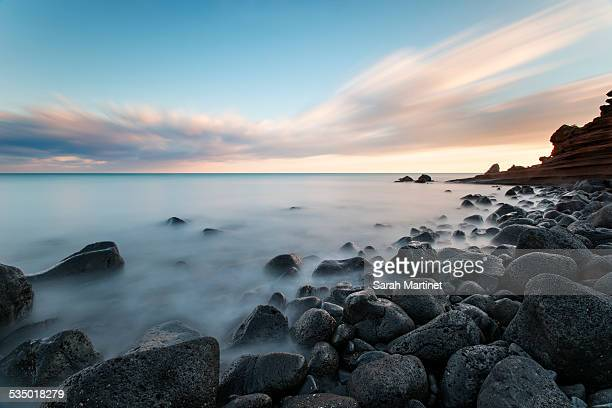 sunset on a rocky beach - cap d'agde stock photos and pictures