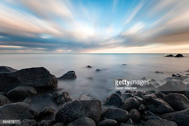 sunset on a rocky volcanic beach - cap d'agde stock photos and pictures