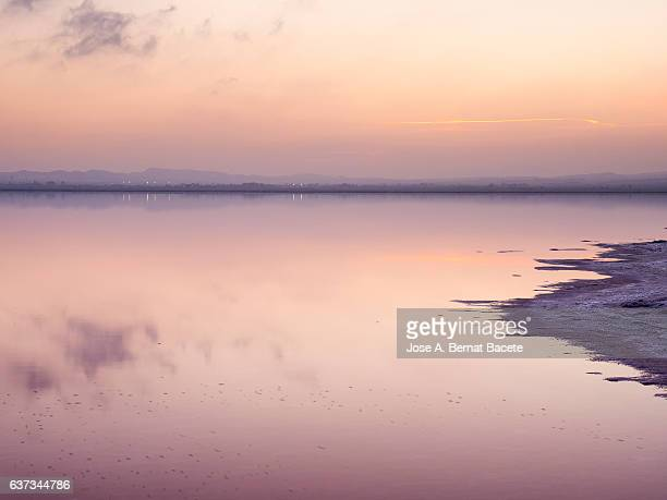 Sunset on a salt lake with calm water pink color  and sky color orange