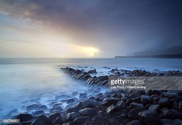 Sunset on a stormy winter's day looking across Kimmeridge Bay from the remains of Clavell's Pier, Kimmeridge, near Swanage, Dorset, England, United Kingdom, Europe