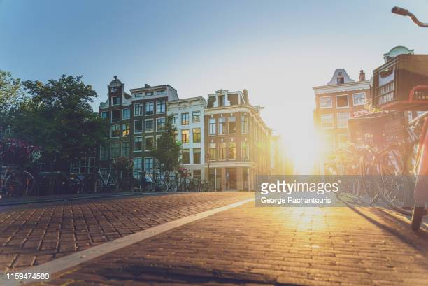 sunset on a street in amsterdam - morning stockfoto's en -beelden