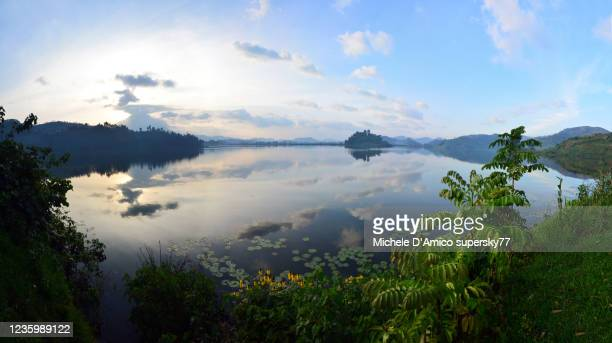 sunset on a tropical lake, with virunga volcanoes in the background - east africa stock pictures, royalty-free photos & images