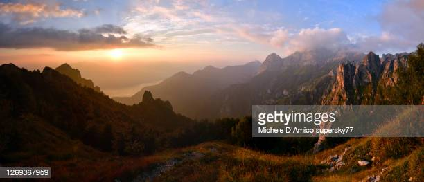 sunset on a wild rocky valley with puffy clouds - area selvatica foto e immagini stock