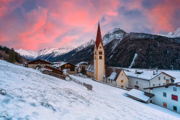 Sunset on alpine village covered with snow, Valle Isarco, Trentino-Alto Adige, Italy