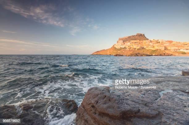 sunset on blue sea, castelsardo, sardinia - rivage photos et images de collection