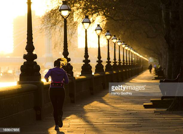 CONTENT] Sunset on Chelsea Embankment A women runs alongside the Thames River getting her evening exercise