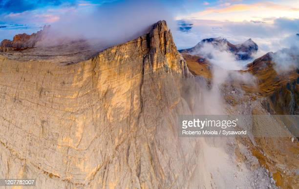 sunset on lastoi de formin in a sea of clouds, giau pass, dolomites, italy - 岩壁 ストックフォトと画像