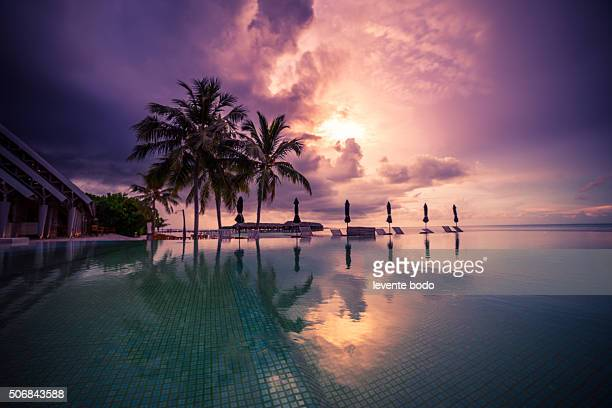Sunset on Maldives island, reflections over the pool