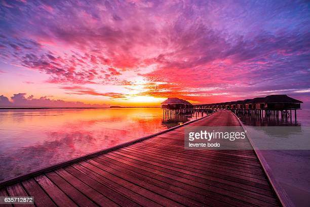 sunset on maldives island, water villas resort. beautiful sky and clouds. beautiful beach background for summer travel with sun, beach wooden jetty. summer mood sun beach background concept. - south asia stock pictures, royalty-free photos & images