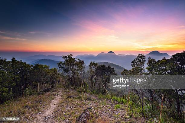 sunset on mountain range - wiratgasem stock photos and pictures