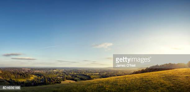 sunset on open hill overlooking country towns panoramic - panoramic stock pictures, royalty-free photos & images