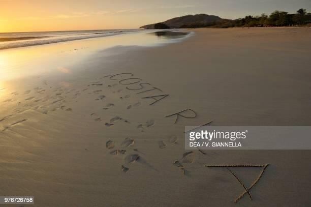 Sunset on Playa Grande beach, writing in the sand, near Tamarindo, Guanacaste, Costa Rica.