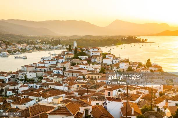 sunset on poros island in aegean sea, greece - peloponnese stock photos and pictures