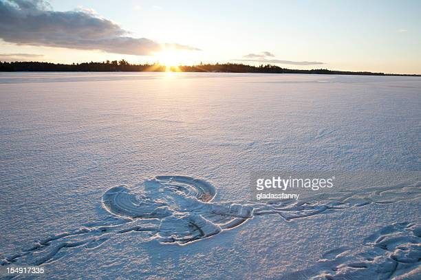 sunset on snow angel - snow angel stock photos and pictures