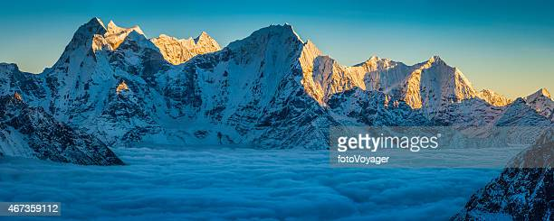 Sunset on snowy mountain peaks panorama above clouds Himalayas Nepal