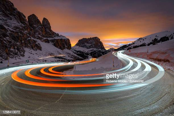 sunset on snowy sassolungo and car trails lights, south tyrol - traffic stock pictures, royalty-free photos & images