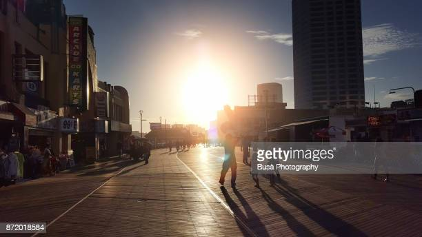 Sunset on the Atlantic City Boardwalk, with pedestrians walking