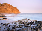 Sunset on the beach and rocky coast of the Cabo de Gata with formations of volcanic rock.  Cabo de Gata - Nijar Natural Park, Cala Mosul, Beach, Biosphere Reserve, Almeria,  Andalusia, Spain