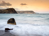 Sunset on the beach and rocky coast of the Cabo de Gata with formations of volcanic rock.  Cabo de Gata - Nijar Natural Park, Cala del Cuervo, Biosphere Reserve, Almeria,  Andalusia, Spain