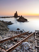 Sunset on the beach and rocky coast of the Cabo de Gata with formations of volcanic rock and with the metallic ancient rails to throw the ships of fishing. Cabo de Gata - Nijar Natural Park, Sirens reef, Biosphere Reserve, Almeria,  Andalusia, Spain