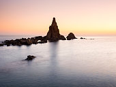 Sunset on the beach and rocky coast of the Cabo de Gata with formations of volcanic rock.  Cabo de Gata - Nijar Natural Park, Sirens reef, Beach, Biosphere Reserve, Almeria,  Andalusia, Spain