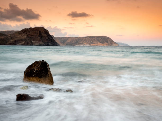 Sunset on the beach and rocky coast of the Cabo de Gata with formations of volcanic rock and the water of the sea in movement Cabo de Gata - Nijar Natural Park, Cala del Cuervo, Beach, Biosphere Reserve, Almeria,  Andalusia, Spain