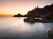 Sunset on the beach and rocky coast with the silhouette of big cliffs and a lighthouse . Cabo de Gata - Nijar Natural Park, Sirens reef, Biosphere Reserve, Almeria,  Andalusia, Spain