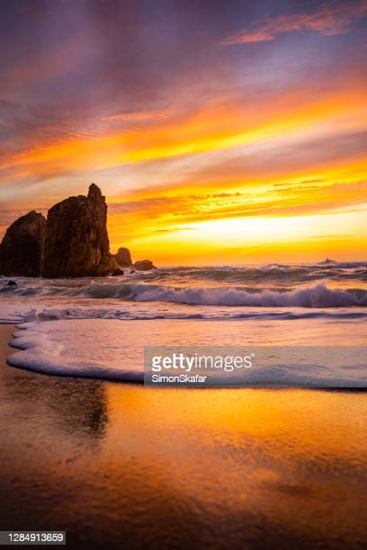 sunset on the beach - rocky coastline stock pictures, royalty-free photos & images