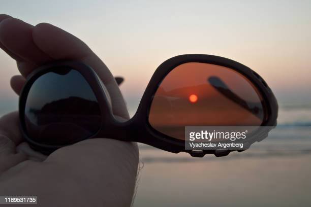 sunset on the beach through eyeglasses, trance culture in vagator, goa, india - argenberg stock pictures, royalty-free photos & images