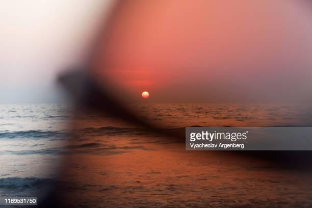 sunset on the beach through eyeglasses, trance culture in vagator, india - argenberg stock-fotos und bilder