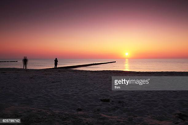 sunset on the beach with two people - sunset beach stock photos and pictures