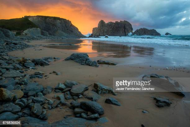 A sunset on the coast of the Cantabrian Sea just after a storm leaves a beautiful sky with warm and cold tones at the same time. On the beach of Arnía, Liencres, Cantabria, Spain.
