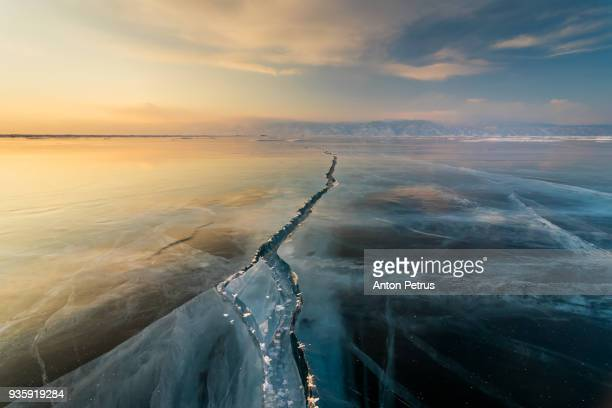 Sunset on the ice with cracks. Baikal, winter