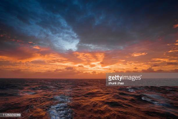sunset on the ocean - moody sky stock pictures, royalty-free photos & images
