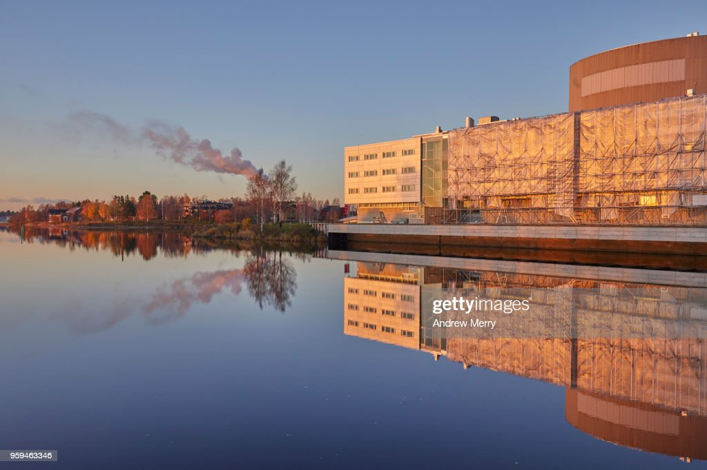 Sunset on the Oulujoki River with blue sky, new buildings, smokestacks and smoke clouds reflected in the water, Oulu, Finland : Stock Photo
