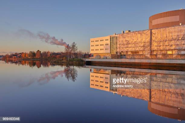 Sunset on the Oulujoki River with blue sky, new buildings, smokestacks and smoke clouds reflected in the water, Oulu, Finland