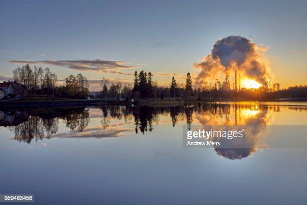 Sunset on the Oulujoki River with blue sky, smokestacks and smoke clouds reflected in the water, Oulu, Finland