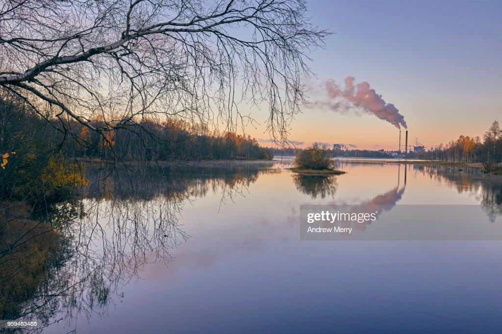 Sunset on the Oulujoki River with blue sky, smokestacks and smoke clouds reflected in the water, Oulu, Finland : Stock Photo