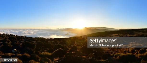 sunset on the shira plateau, with mount meru above the fog layer - meru filme stock-fotos und bilder