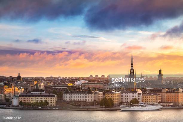 sunset or sunrise sky over riddarholmen chruch in gamla stan old town with boat for transportation in water and view of stockholm city, where is the popular landmark for travel stockholm, sweden, europe - capital cities stock pictures, royalty-free photos & images