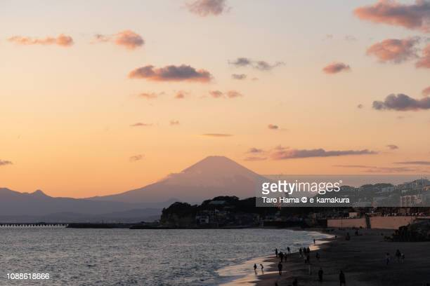 Sunset orange-colored clouds on winter snow-capped Mt. Fuji in Japan