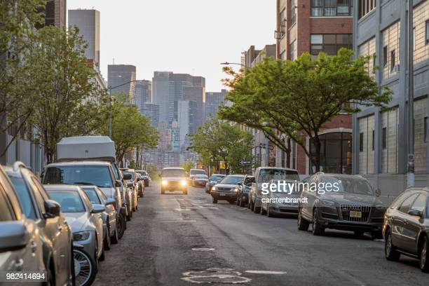 sunset over 43rd avenue in queens with a view to manhattan - pothole stock photos and pictures