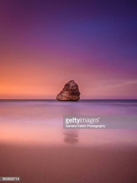 sunset over a beautiful beach - samere fahim stock photos and pictures