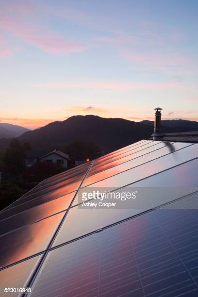 sunset over a house in ambleside, lake district uk, with a 3.8 kw solar panel system on the roof. - roof stock pictures, royalty-free photos & images