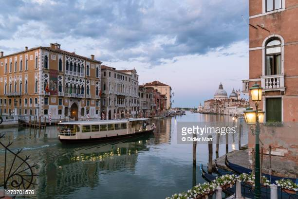 sunset over a vaporetto sailing on the famous grand canal in venice - vaporetto stock pictures, royalty-free photos & images