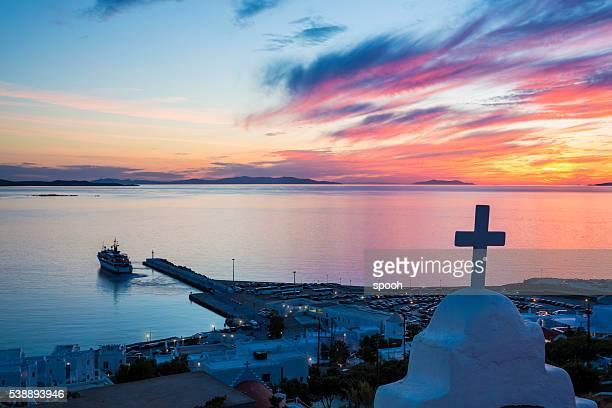 Coucher de soleil sur la mer Égée et de Mykonos terminal de ferry (Grèce).