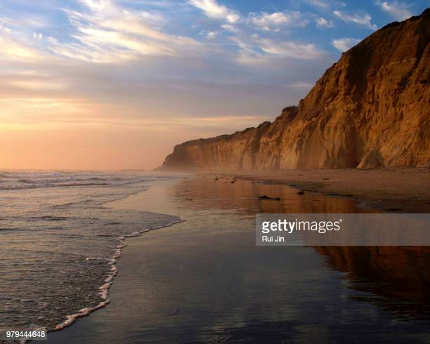 sunset over beach with rocky mountain, torrey pines state park, california, usa - california beach stock pictures, royalty-free photos & images