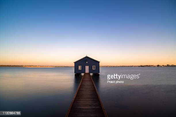 sunset over blue boathouse in the swan river in perth, western australia, australia. - perth australia stock pictures, royalty-free photos & images