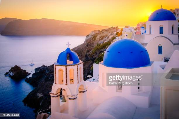 Sunset over blue dome church tops and volcanic landscape in Santorini
